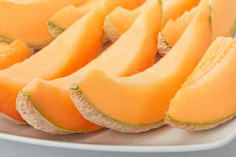 Melon de cantaloup, tranches oranges sur le plat photographie stock