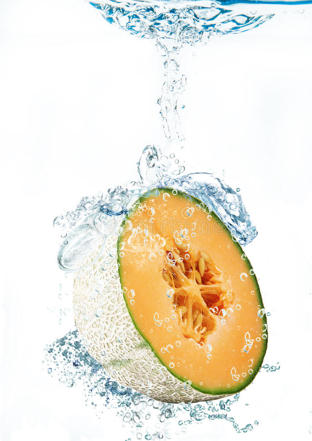 Melon falling in water stock photo