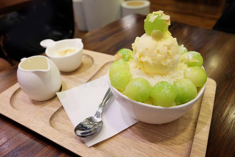 Melon Korean Shaved Ice Cream Vanilla Dessert on Tray with Topping and Milk on Wooden Table Background. Great for Any Use royalty free stock photos