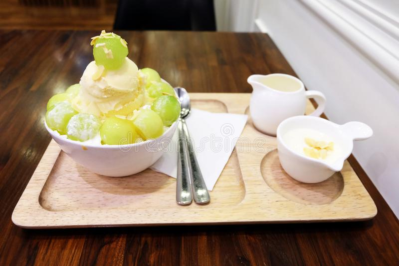 Melon Korean Shaved Ice Cream Vanilla Dessert on Tray with Topping and Milk on Wooden Table Background. Great for Any Use stock photo