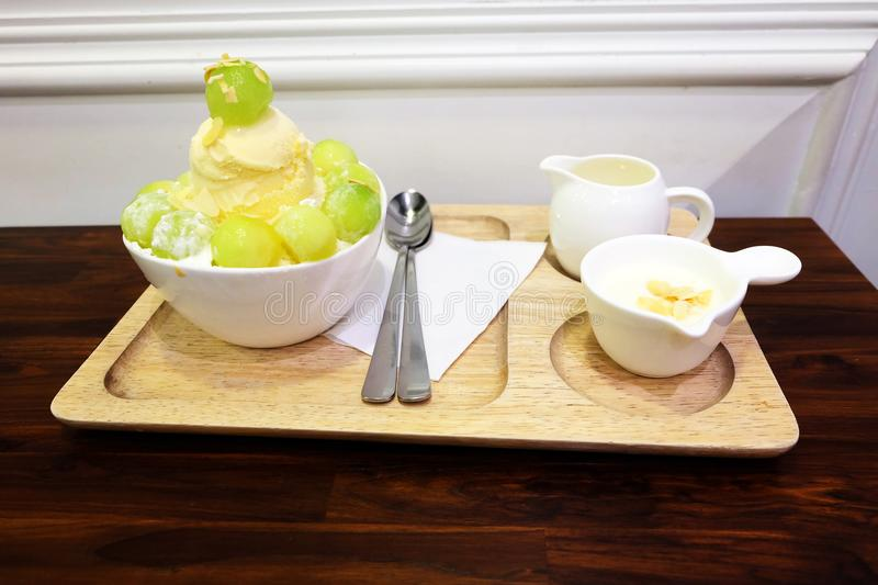 Melon Korean Shaved Ice Cream Vanilla Dessert on Tray with Topping and Milk on Wooden Table Background. Great for Any Use stock photos