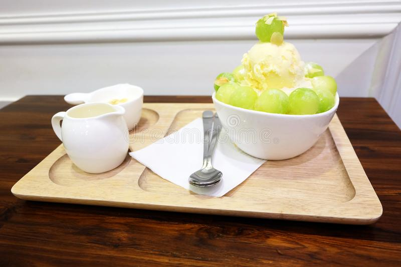 Melon Korean Shaved Ice Cream Vanilla Dessert on Tray with Topping and Milk on Wooden Table Background. Great for Any Use stock image