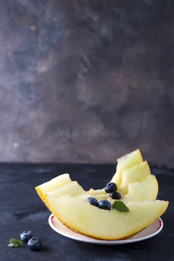 Melon mûr coupé en tranches d'un plat sur un fond en pierre foncé photographie stock
