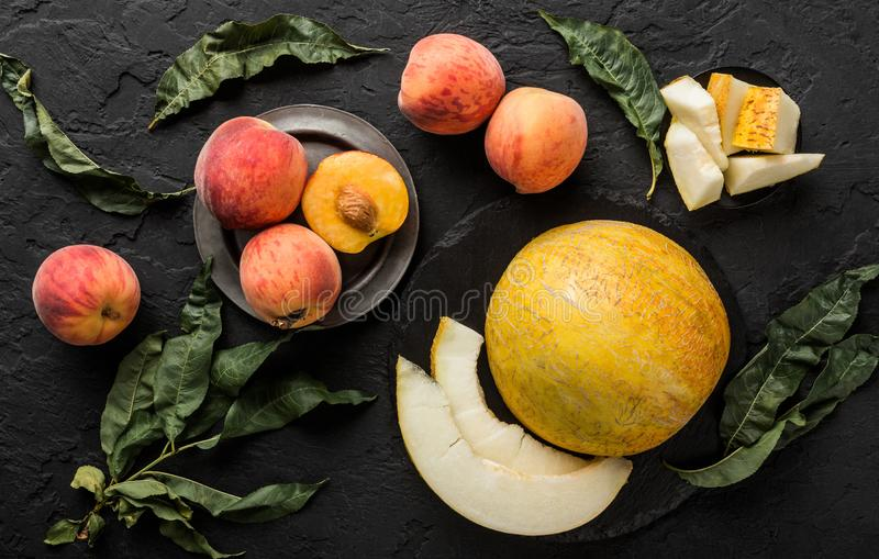Melon and peaches. Creative layout made of fruits. Colorful fresh fruit on black stone background. Top view stock images