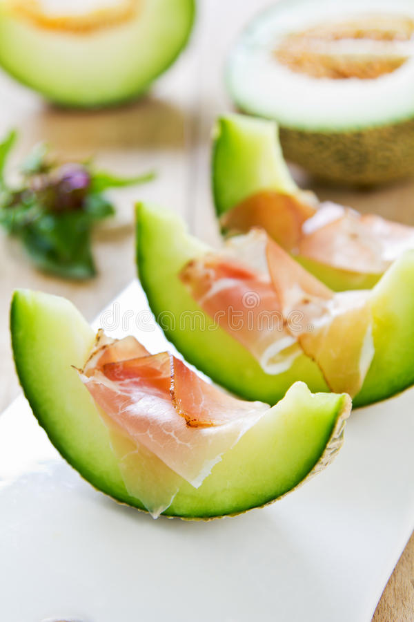 Melon with Prosciutto. Fresh Melon with Prosciutto and basil royalty free stock photo