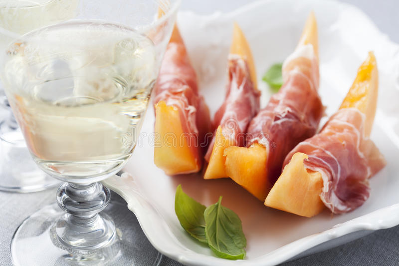 Melon and prosciutto. Slices of cantaloupe melon and prosciutto ham, shallow DOF royalty free stock photos