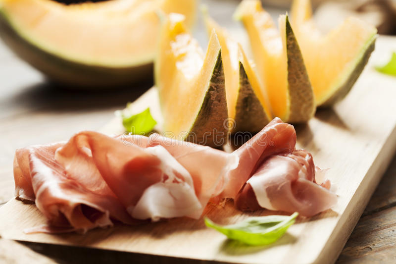 Melon and prosciutto. Slices of cantaloupe melon and prosciutto ham, shallow DOF stock photo