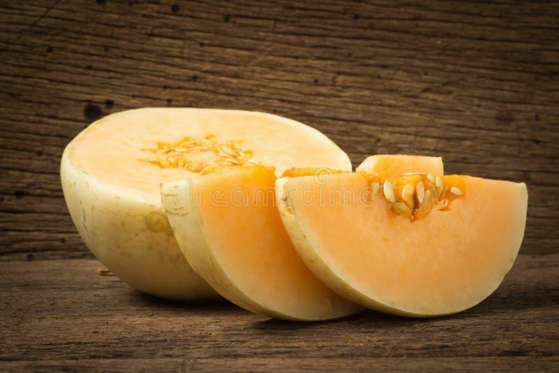 melon ( sunlady) skiva half På gammalt trä Morgon royaltyfri foto