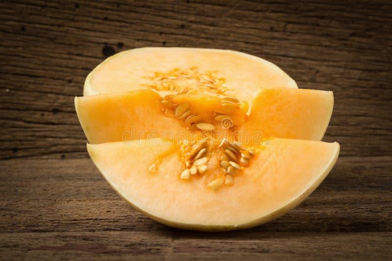 melon ( sunlady) skiva half På gammalt trä Morgon arkivbilder