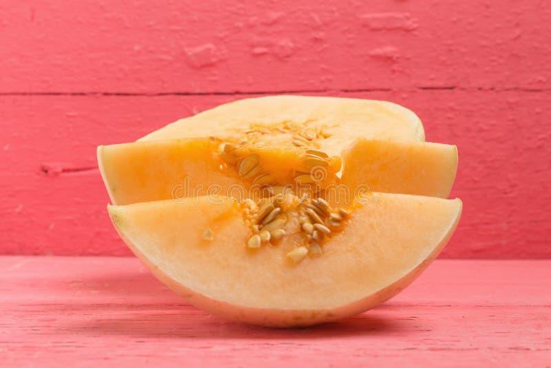 melon ( sunlady) skiva half på wood rosa färger arkivbild