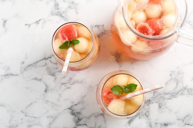 Melon and watermelon ball cocktail with mint served on white marble table. Flat lay royalty free stock photography