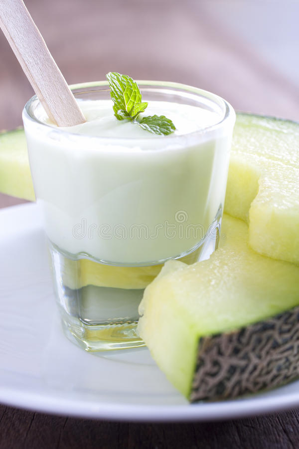 Melon yogurt. Decorate with mint leaves served with melon slices stock images