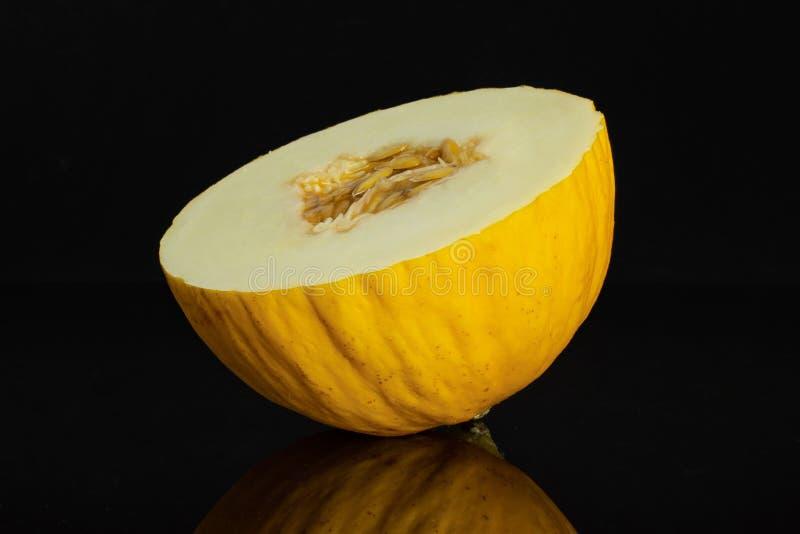 Melone color giallo canarino giallo isolato su vetro nero immagini stock libere da diritti
