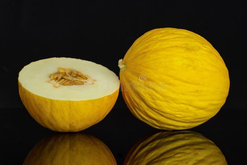 Melone color giallo canarino giallo isolato su vetro nero fotografie stock