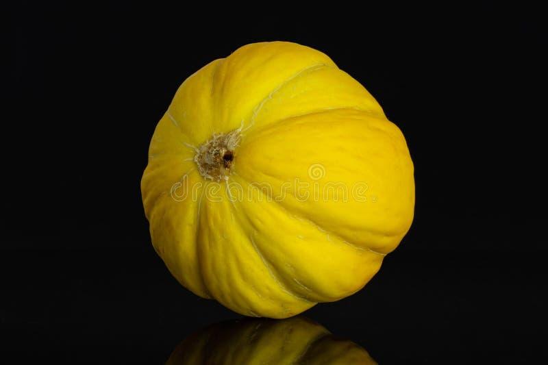 Melone color giallo canarino giallo isolato su vetro nero immagini stock