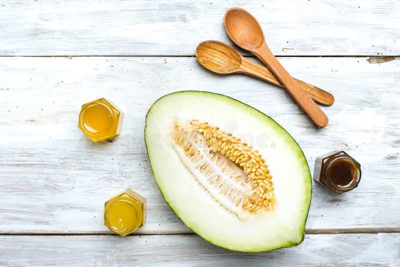 Melonenlöffel und -honig auf weißem Brett lizenzfreies stockfoto