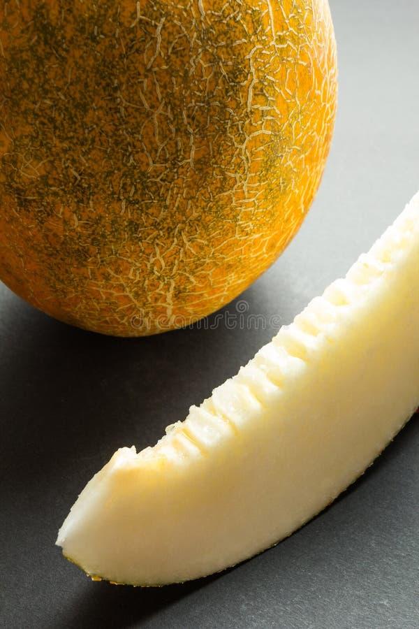Melones org?nicos frescos del cantalupo cortados en el fondo negro, vertical foto de archivo