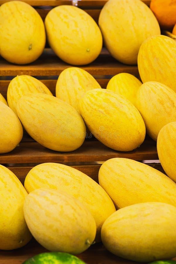 Meloni gialli luminosi su un contatore di legno sul mercato immagini stock libere da diritti