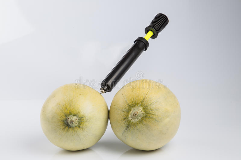 Melons and bicycle pump. Cosmetic treatment metaphor for female breasts: melons air pumped by bicycle pump meaning cosmetic and health treatment isolated on stock photos