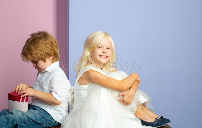 Melt her heart with gift. Friendship and love. Lovely tender children. Small kids friendship. Sincere friendship. Couple. Adorable kids white clothes. Happy royalty free stock photo