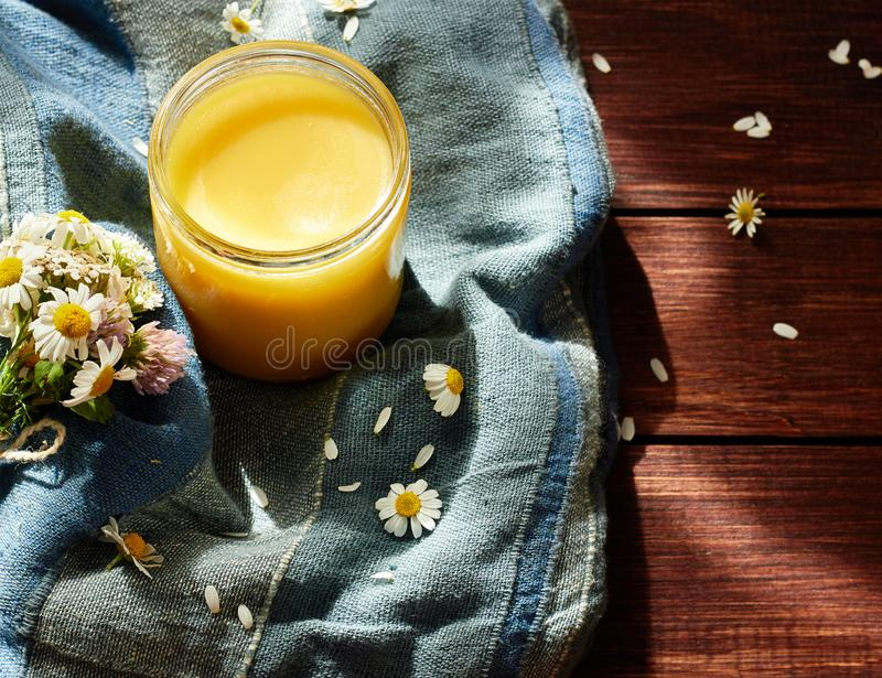 Melted butter ghee in lglass can on textered blue textile. With meadow wild herbs nearby on wooden table,healing ayurvedic remedy and very tasty product for stock photography