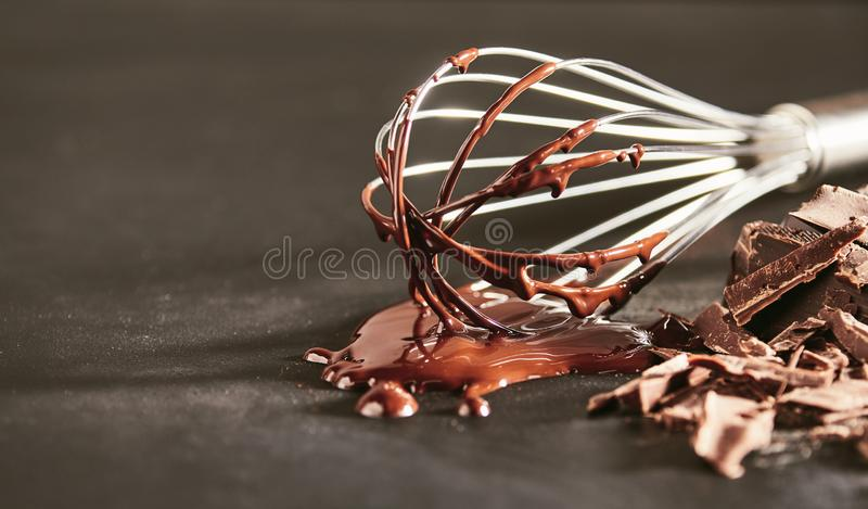 Melted dairy chocolate dripping off an old whisk royalty free stock photos