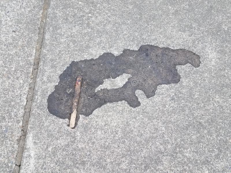 Melted popsicle with stick on grey cement stock images