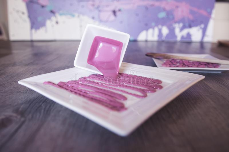 Melted ruby red chocolate in square bone china crockery. Red ruby chocolate buds stock photo