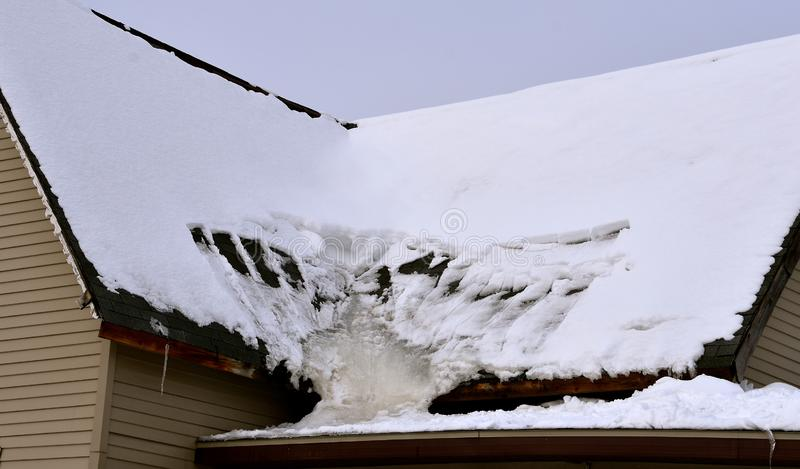 Melted snow creates creates an ice sheet on a roof. Melted snow on a roof has created an ice sheet frozen at an angle royalty free stock photos