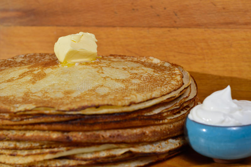 Melting butter pat on a pile of pancakes. Fried pancakes are usually roasted in all Orthodox families for the Orthodox holiday `Maslennitsa`. As a symbol of royalty free stock image