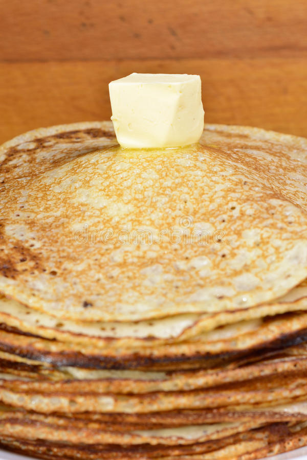 Melting butter pat on a pile of pancakes. Fried pancakes are usually roasted in all Orthodox families for the Orthodox holiday `Maslennitsa`. As a symbol of stock images