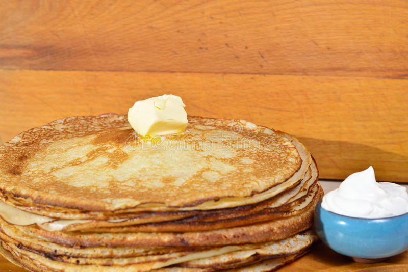Melting butter pat on a pile of pancakes. Fried pancakes are usually roasted in all Orthodox families for the Orthodox holiday `Maslennitsa`. As a symbol of stock photo