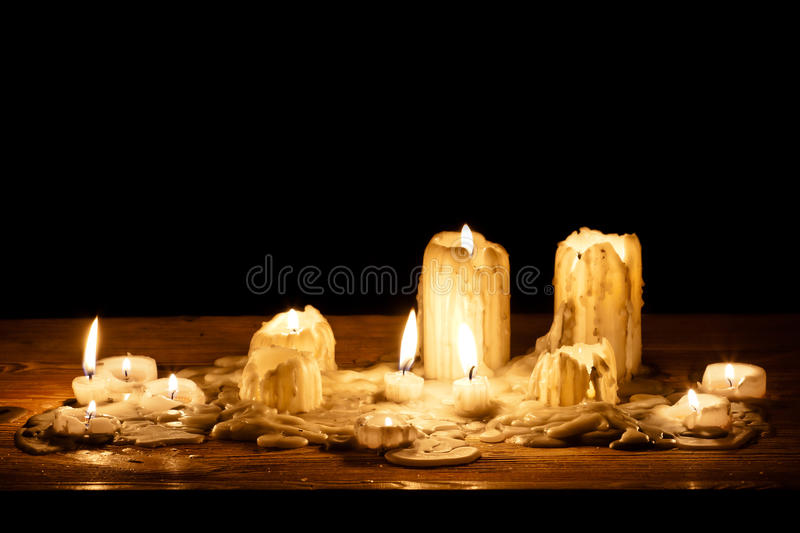 Melting candle in wooden shelf stock images