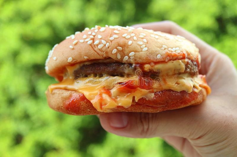 Melting cheese hamburger being held by hand against vibrant green foliage stock photo