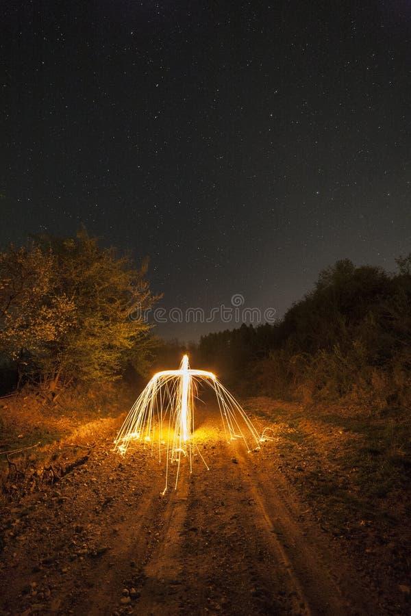 Melting cross under night sky stock photo
