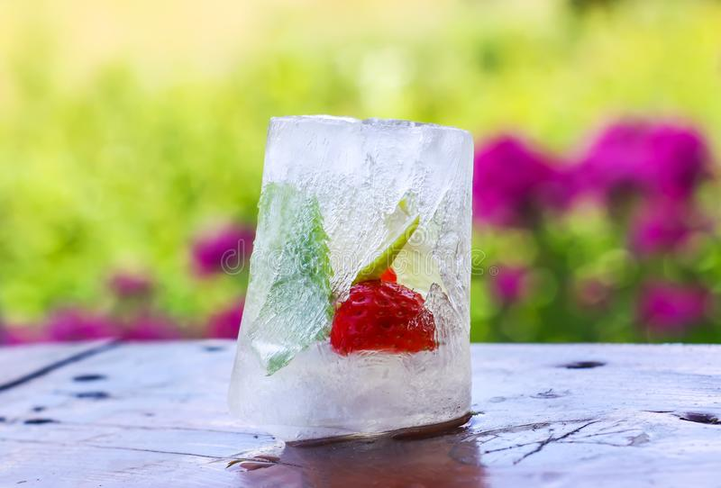 Ice cube with strawberry, lemon and fresh green mint leaves on wooden surface outdoors royalty free stock photography