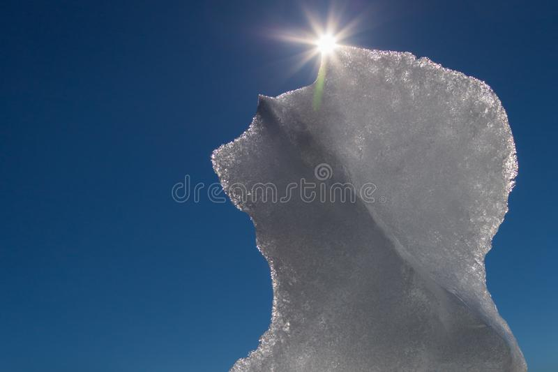 Melting ice floe with sun and blue sky royalty free stock image