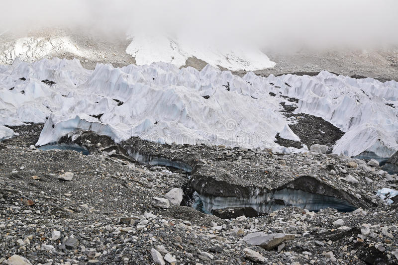 Melting ice glaciers due to global warming with thick mist at the top royalty free stock images