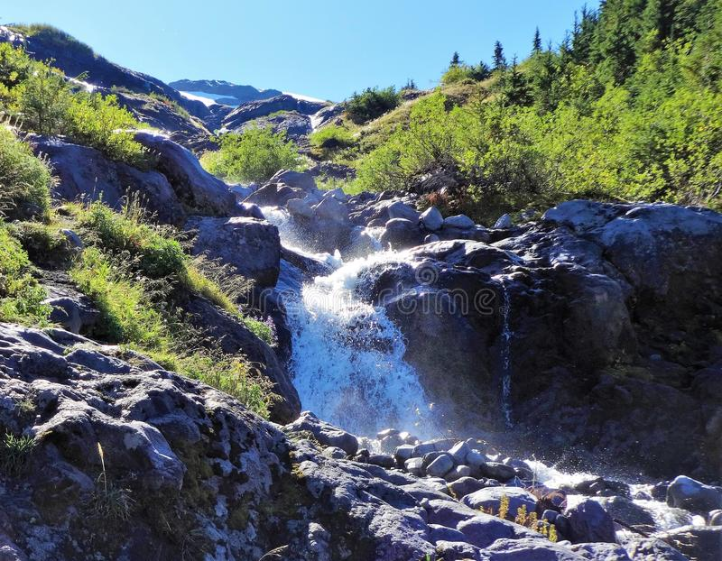 A waterfall cross on Heliotrope Ridge trail, Mount Baker. Melting ice water from Coleman Glacier runs to a waterfall of Heliotrope Creek on Mount Baker stock photos
