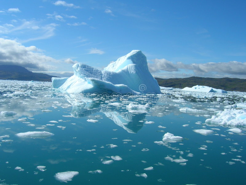 Melting iceberg at the coast of Greenland. Iceberg floating in the sea at the coast of Greenland a beautiful summer day. For similar pictures