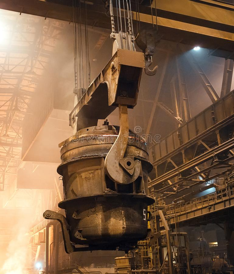 Melting of metal in a steel plant. High temperature in the melting furnace. Metallurgical industry. Factory for the manufacture of metal pipes. Bucket for stock image