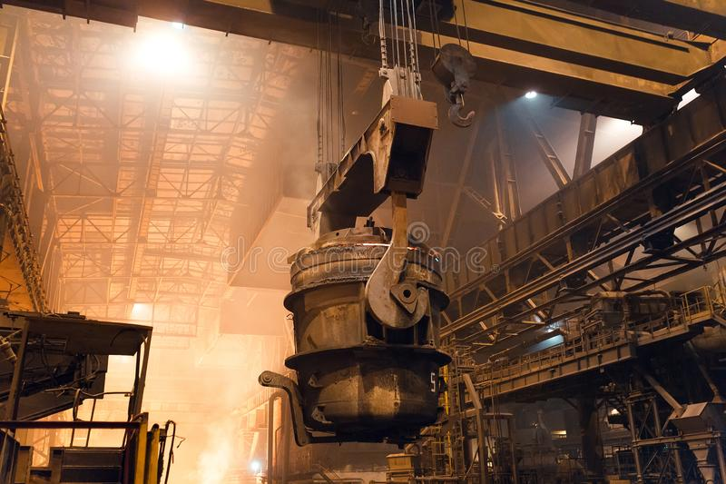 Melting of metal in a steel plant. High temperature in the melting furnace. Metallurgical industry. Factory for the manufacture of metal pipes. Bucket for royalty free stock photo