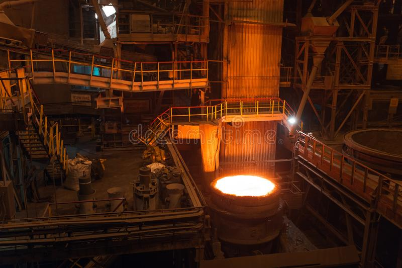 Melting of metal in a steel plant. High temperature in the melting furnace. Metallurgical industry. Factory for the. Manufacture of metal pipes. Bucket for stock photography