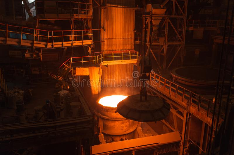 Melting of metal in a steel plant. High temperature in the melting furnace. Metallurgical industry. Factory for the. Manufacture of metal pipes. Bucket for royalty free stock images