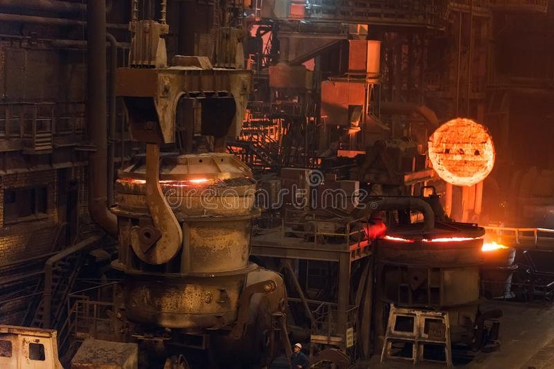 Melting of metal in a steel plant. High temperature in the melting furnace. Metallurgical industry. Factory for the. Manufacture of metal pipes. Bucket for stock image