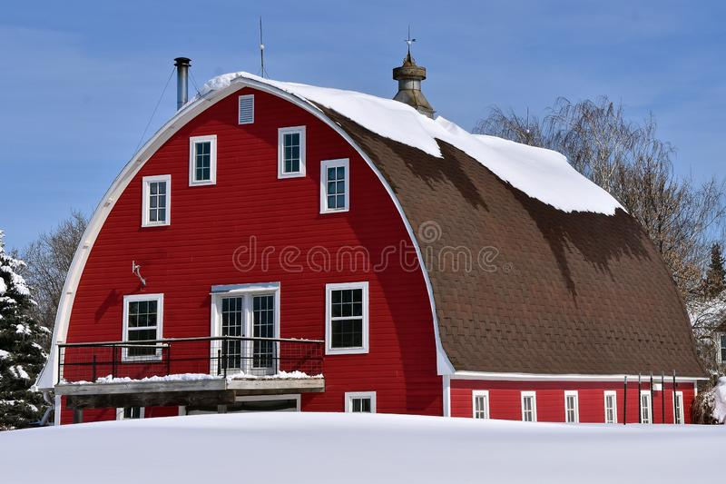 Melting snow on roof of an old red barn stock photos