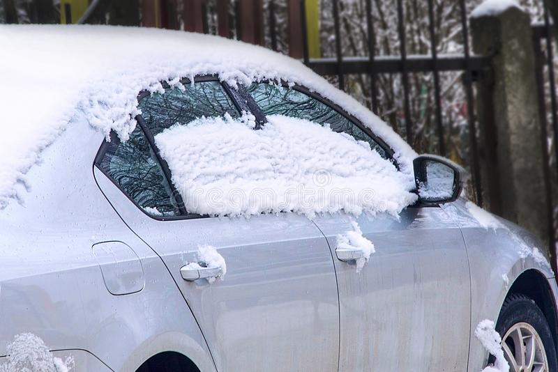 Melting snow on the roof and windows of the car. stock images
