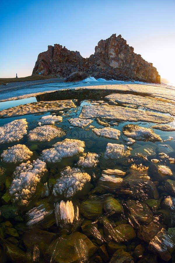 Melting spring ice of Lake Baikal, on the rock Shamanka at sunset royalty free stock photos