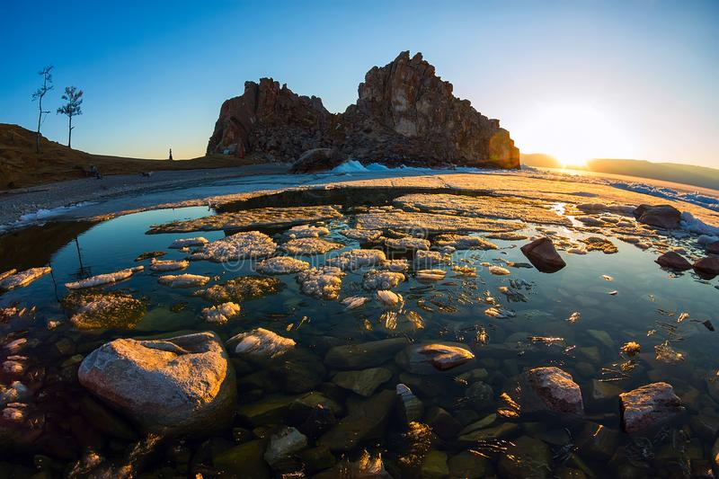 Melting spring ice of Lake Baikal, on the rock Shamanka at sunset stock photo