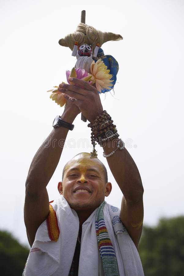 Festival of the Chariots. Member of the Hare Krishna community holds up flowers during the Festival of the Chariots royalty free stock photography